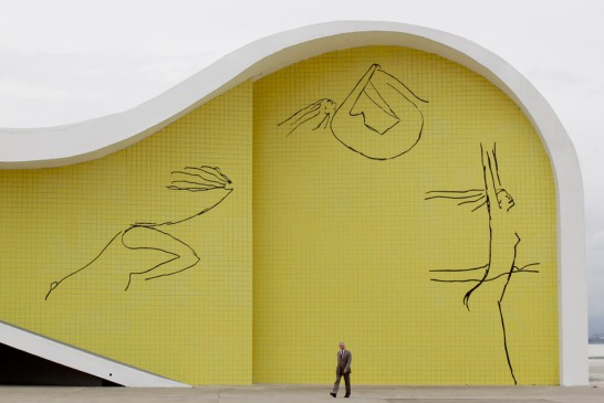 A-man-walks-past-a-building-designed-by-the-Brazilian-architect-Oscar-Niemeyer