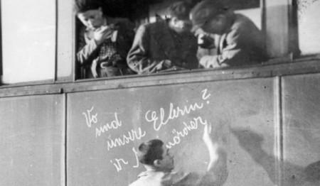 1945, απελευθέρωση. Τρένο στον σταθμό της Βαϊμάρης μεταφέρει παιδιά που επιβίωσαν στο Άουσβιτς. Ένα παιδί γράφει με κιμωλία: «Πού είναι οι γονείς μας; Δολοφόνοι!»