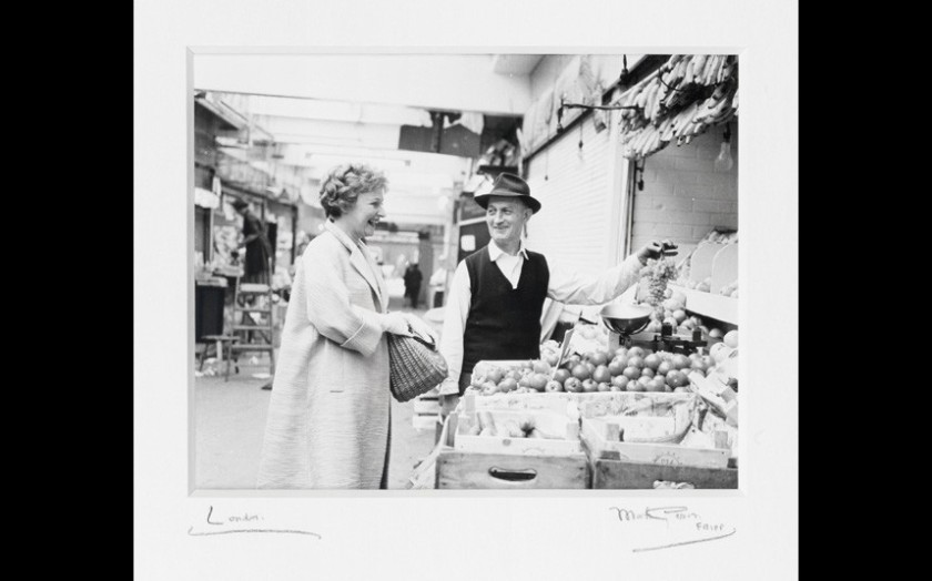 Muriel Spark buying grapes from a shopkeeper in Rome, 1963.