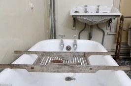 Επιδαπέδια μπανιέρα — για πρώτη φορά. Η ελαφρόπετρα, οι μπάρες σαπουνιών από αχλάδι και η βούρτσα τριψίματος είναι όλα τοποθετημένα πάνω στο ξύλινο ράφι μπάνιου κοντά στον περίτεχνο νιπτήρα.