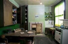 Δεν υπάρχουν σύγχρονες συσκευές εδώ. Η κουζίνα στο Νο 7 της Blyth Grove λειτουργεί με ζωντανή φλόγα. Παλαιού τύπου νεροχύτης και ξύλινα ράφια. Το σίδερο και ο βραστήρας ζεσταίνονται στη σόμπα.