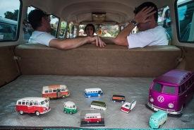 Exhibitors rest inside a Volkswagen Kombi minibus with toy models
