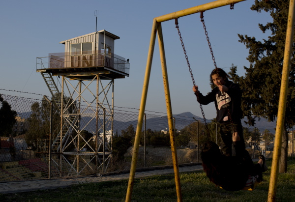 Children play in a park next to a fence marking the United Nations buffer zone in a partially restricted area in the Turkish Cypriot controlled area of central Nicosia