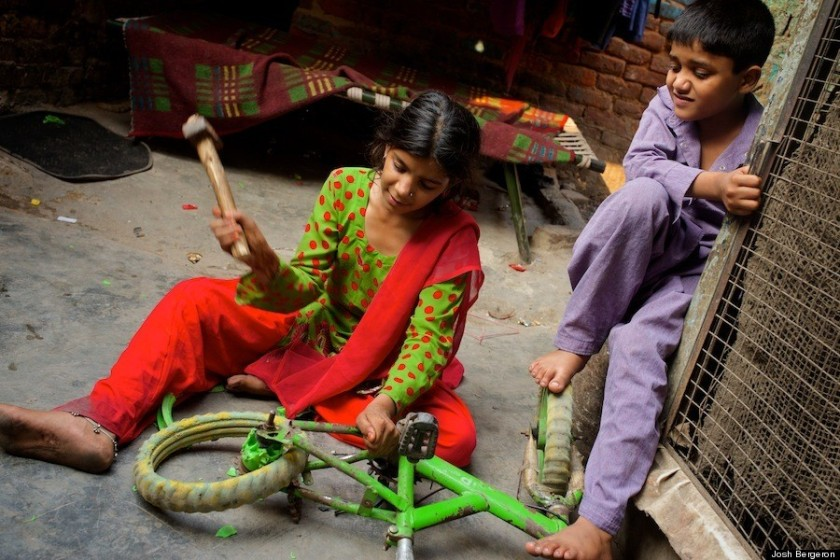 Children dismantle a bicycle to sell for parts.