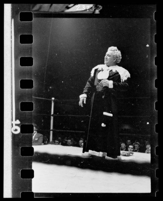 Gorgeous George, full-length portrait, standing in wrestling ring, facing left