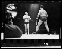 A wrestler strides toward Gorgeous George who stands near a corner of the ring with his hands on his chest where he had received a blow in the previous maneuver in the wrestling match