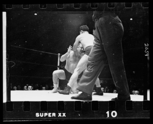 A wrestler holding Gorgeous George by the chin and back of the head, executing a maneuver during a wrestling match