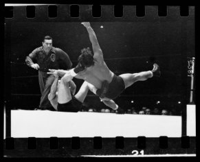 Two men wrestling with a referee nearby