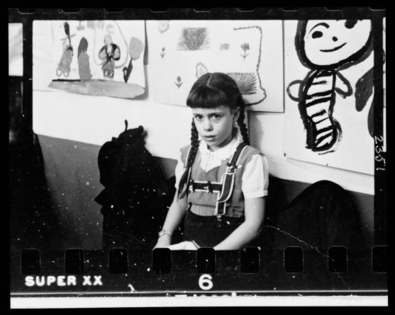 Young girl, half-length portrait, standing against wall displaying art work, in classroom in Chicago, Illinois