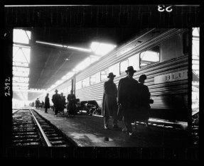 Men, probably commuters, walking along a platform next to a train