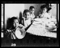 African American children seated around a table in an apartment, eating