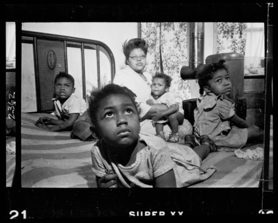 An African American woman and several children sitting on a bed in an apartment