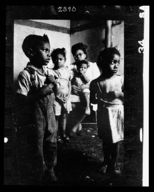 African American mother and her four children in their tenement apartment