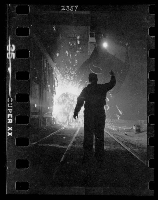 Steel worker in mill as molten steel spills from vat, in Chicago, Illinois