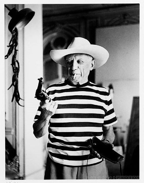 Rene_Burri_Picasso_with_revolver_and_hat_of_Gary_Cooper_Cannes_1958