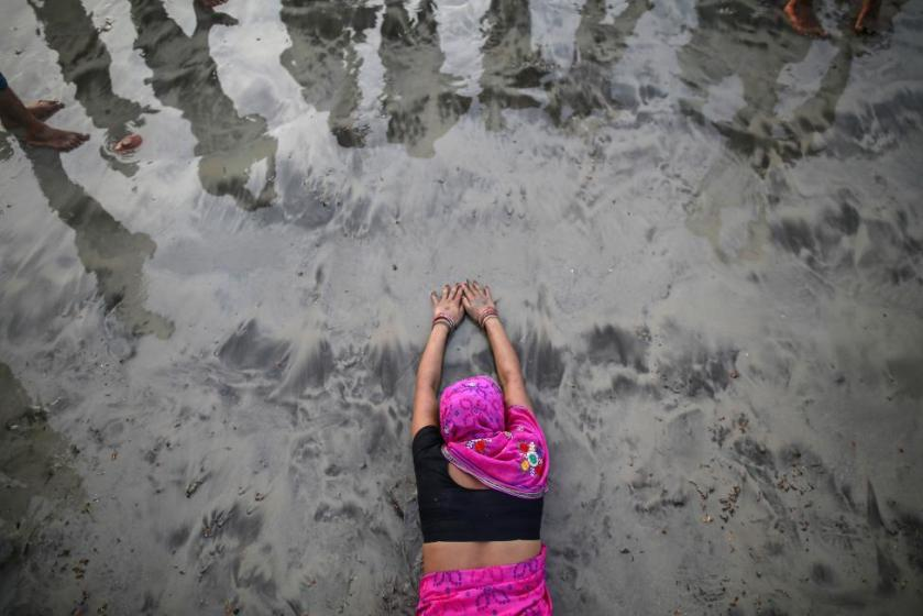 """A Hindu devotee lies along the shores of the Arabian Sea as she offers prayers to the Sun god during the """"Chhat"""" festival in Mumbai"""
