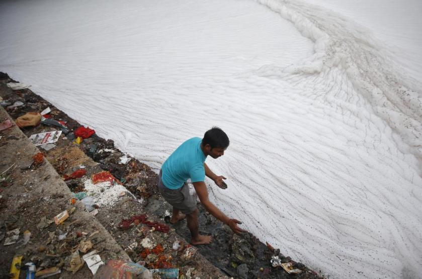 Man cleans the stairs on the banks of polluted river Yamuna before Hindu devotees started worshipping the Sun god Surya during the Hindu religious festival of Chatt Puja in New Delhi