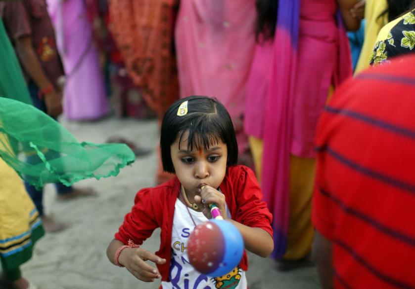 A girl blows a balloon pipe during the Hindu religious festival of Chatt Puja in New Delhi