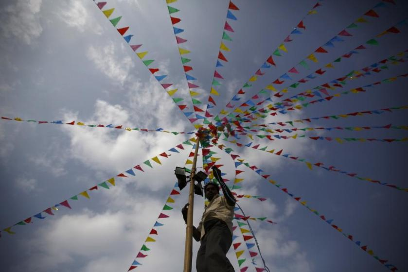 """A man fits a light on a bamboo pole during the """"Chhat"""" festival near the bank of Bagmati River in Kathmandu"""