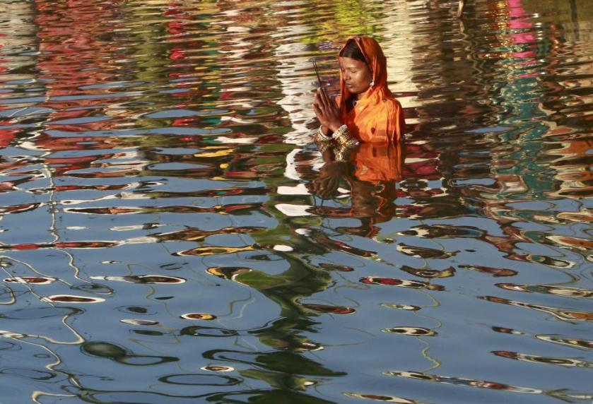 A woman worships the Sun god Surya in the waters of the Laxmi Narayan lake during the Hindu religious festival of Chatt Puja in Agartala