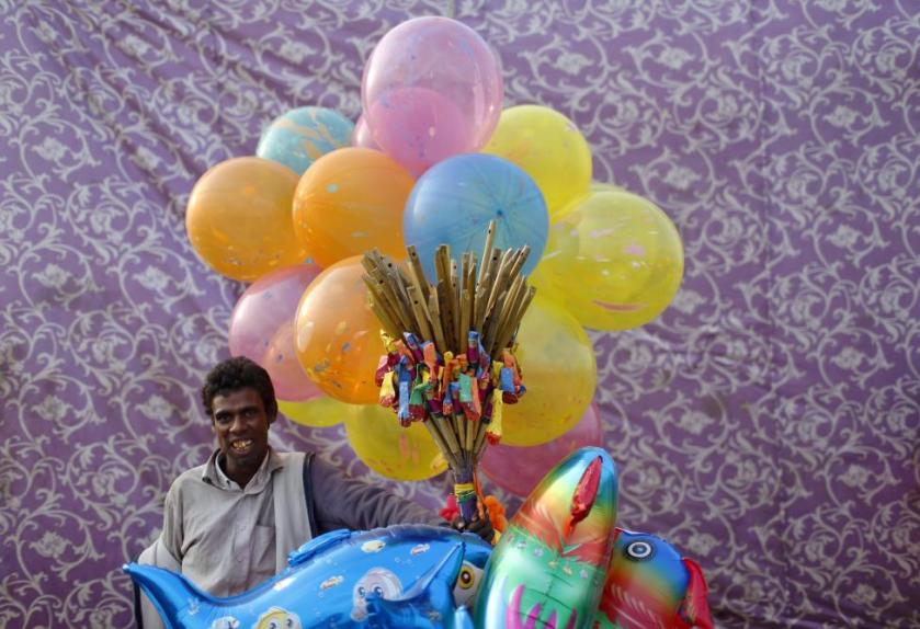 A vendor selling balloons waits for customers on the banks of the river Yamuna during the Hindu religious festival of Chatt Puja in New Delhi