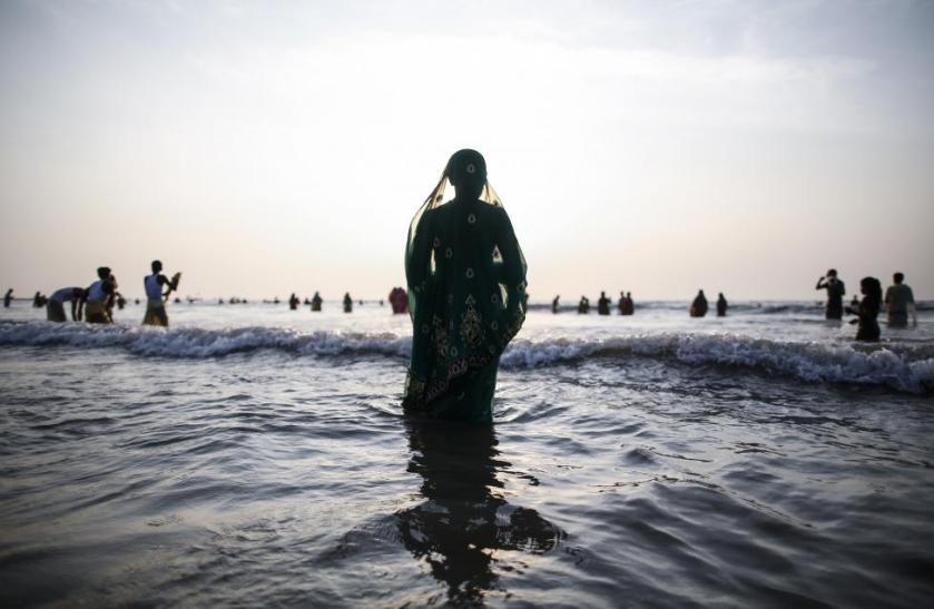 """A Hindu devotee prays while standing in the waters of the Arabian Sea as she worships the Sun god Surya during the Hindu religious festival """"Chatt Puja"""" in Mumbai"""