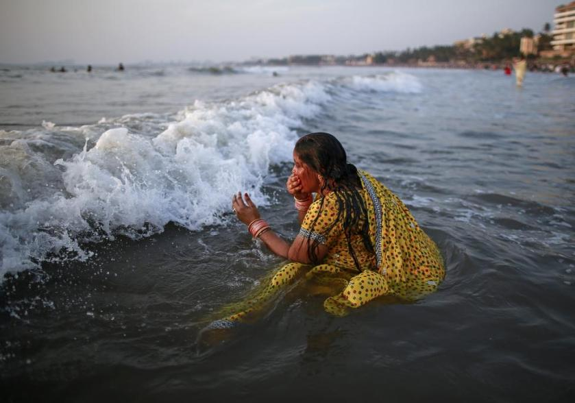 """A Hindu devotee takes a dip in the waters of the Arabian Sea as she worships the Sun god Surya during the Hindu religious festival """"Chatt Puja"""" in Mumbai"""