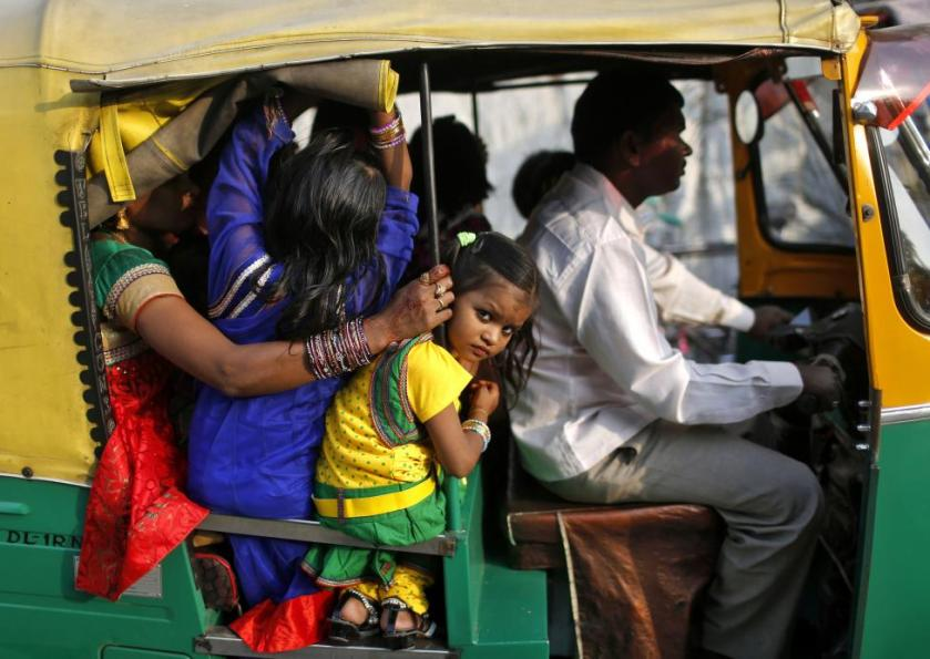 A girl peeps out from an auto rickshaw as she arrives with her family to worship the Sun god Surya during the Hindu religious festival of Chatt Puja in New Delhi