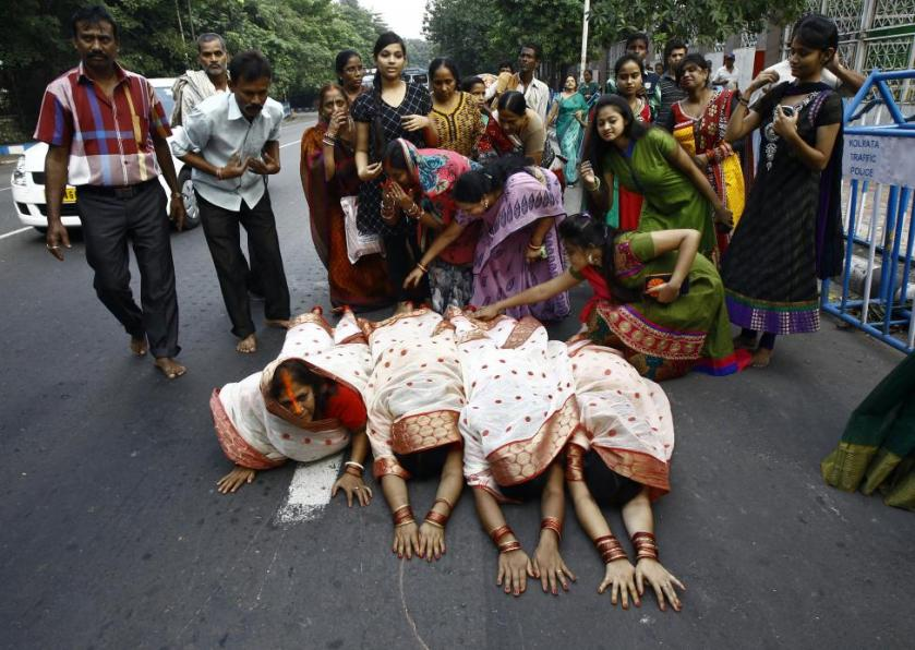 Hindu devotees lie on a road as they worship the Sun god Surya during the Hindu religious festival of Chatt Puja in Kolkata