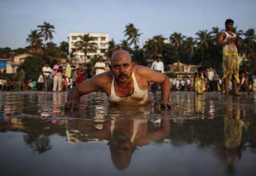 """A Hindu devotee lies along the shores of the Arabian Sea as he offers prayers to the Sun god during the """"Chhat"""" festival in Mumbai"""