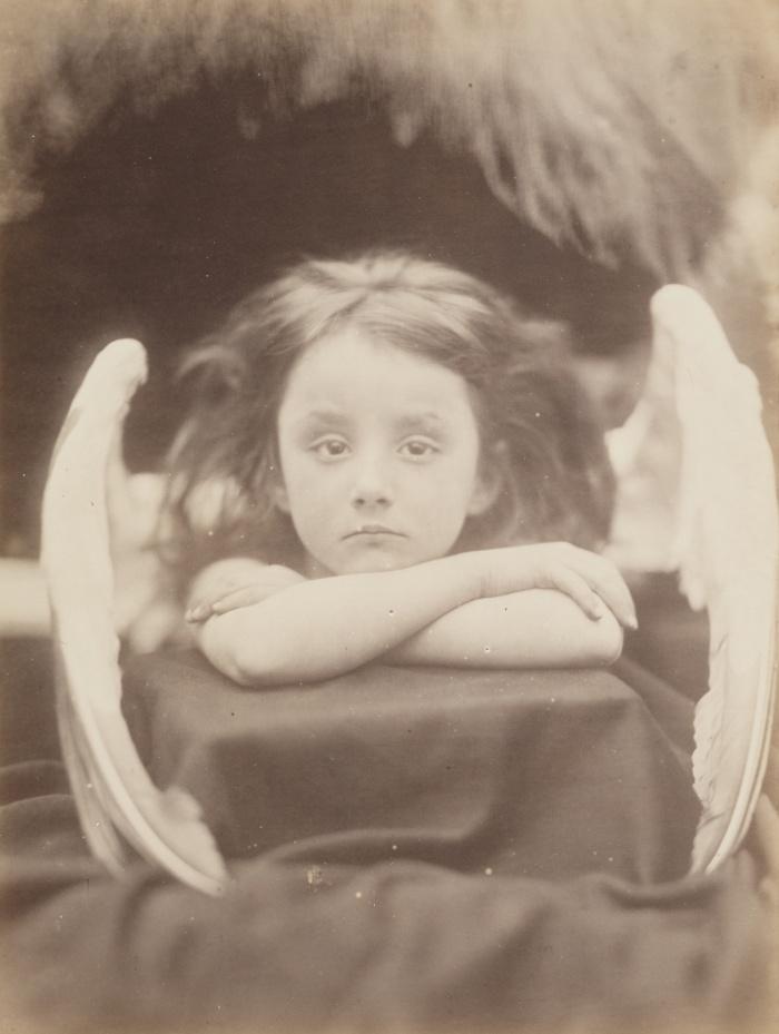 Περιμένω, 1872, Τζούλια Μάργκαρετ Κάμερον (by Julia Margaret Cameron). Η Κάμερον, μία από τις πρωτοπόρους γυναίκες φωτογράφους της εποχής της, άρχισε να ασχολείται με τη φωτογραφία στην ηλικία των 48 ετών.  Είχε το στούντιο της σ' ένα διαμορφωμένο κοτέτσι στο πίσω μέρος του κήπου του σπιτιού της στο Isle of Wight, κι εκεί τράβηξε τα πορτρέτα διάσηπων προσωπικοτήτων της βικτωριανής εποχής, από τον Άλφρεντ Τένισον έως τον Κάρολο Δαρβίνο. Η συγκεκριμένη φωτογραφία της ανηψιάς της Rachel Gurney να φοράει φτερά κύκνου, παραπέμπει σε αναγεννησιακό ερωτιδέα.
