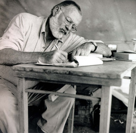 HFA XKRT KRT ENTERTAINMENT STORY SLUGGED: HEMINGWAY KRT PHOTOGRAPH COURTESY OF THE JOHN F. KENNEDY LIBRARY (KRT119-July 19) Ernest Hemingway writing at a desk while on safari in 1953. This picture is included in the exhibition