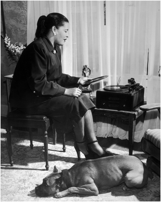 circa 1945: EXCLUSIVE American jazz vocalist Billie Holiday (1915-1959) sitting by a window and holding a record, with a dog lying at her feet. (Photo by Metronome/Getty Images)